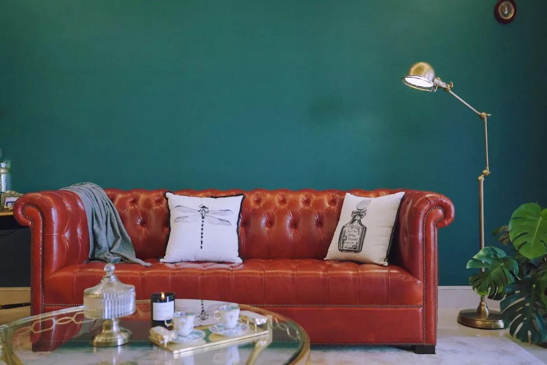 Sự kết hợp giữa sofa da đỏ và màu tường xanh đậm cùng cây đèn đứng mang nét cổ điển.